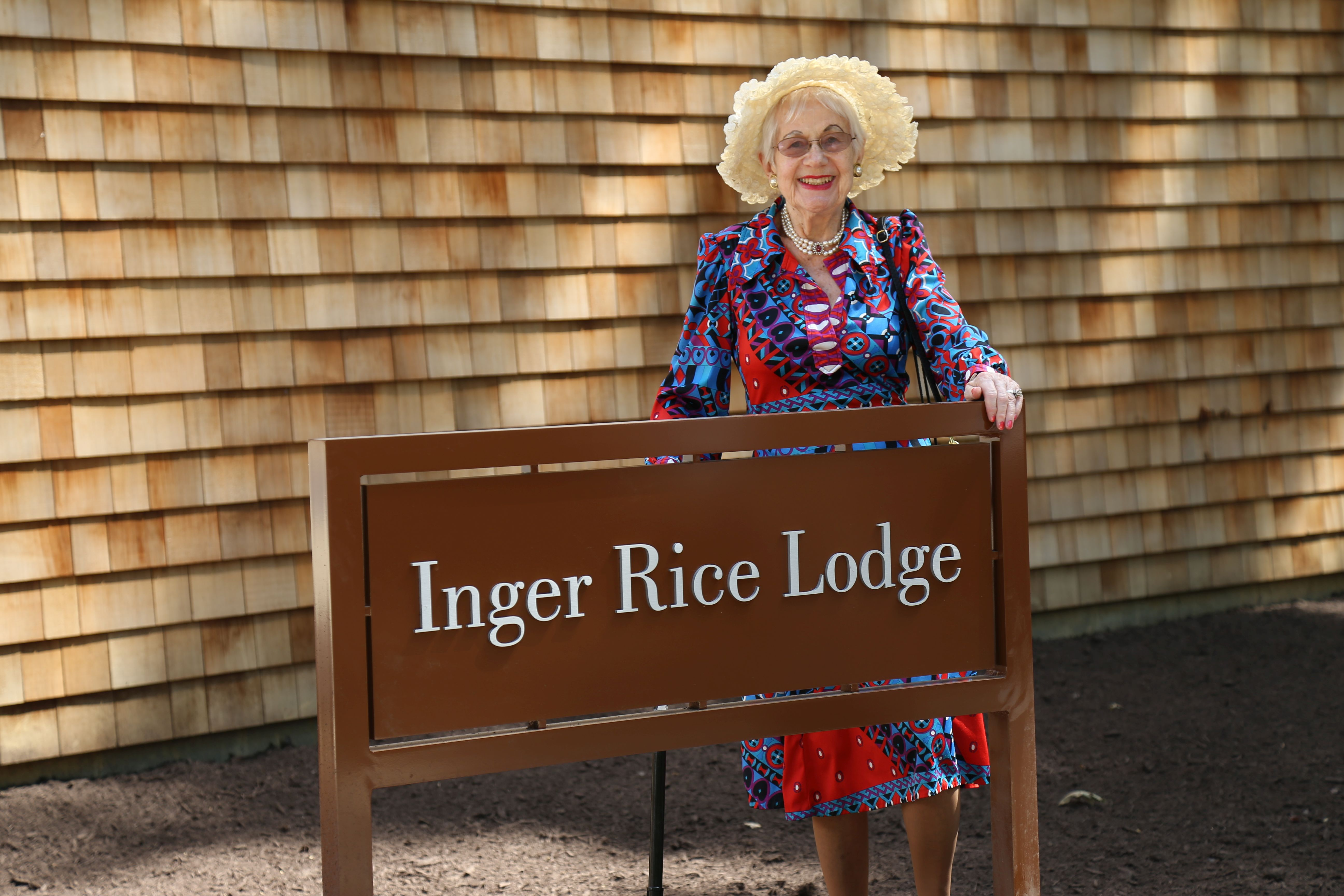 Inger Rice, A.M., in front of the sign to the Inger Rice Lodge