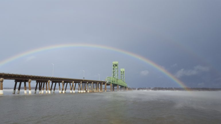 A rainbow arches over a bridge that crosses the James River