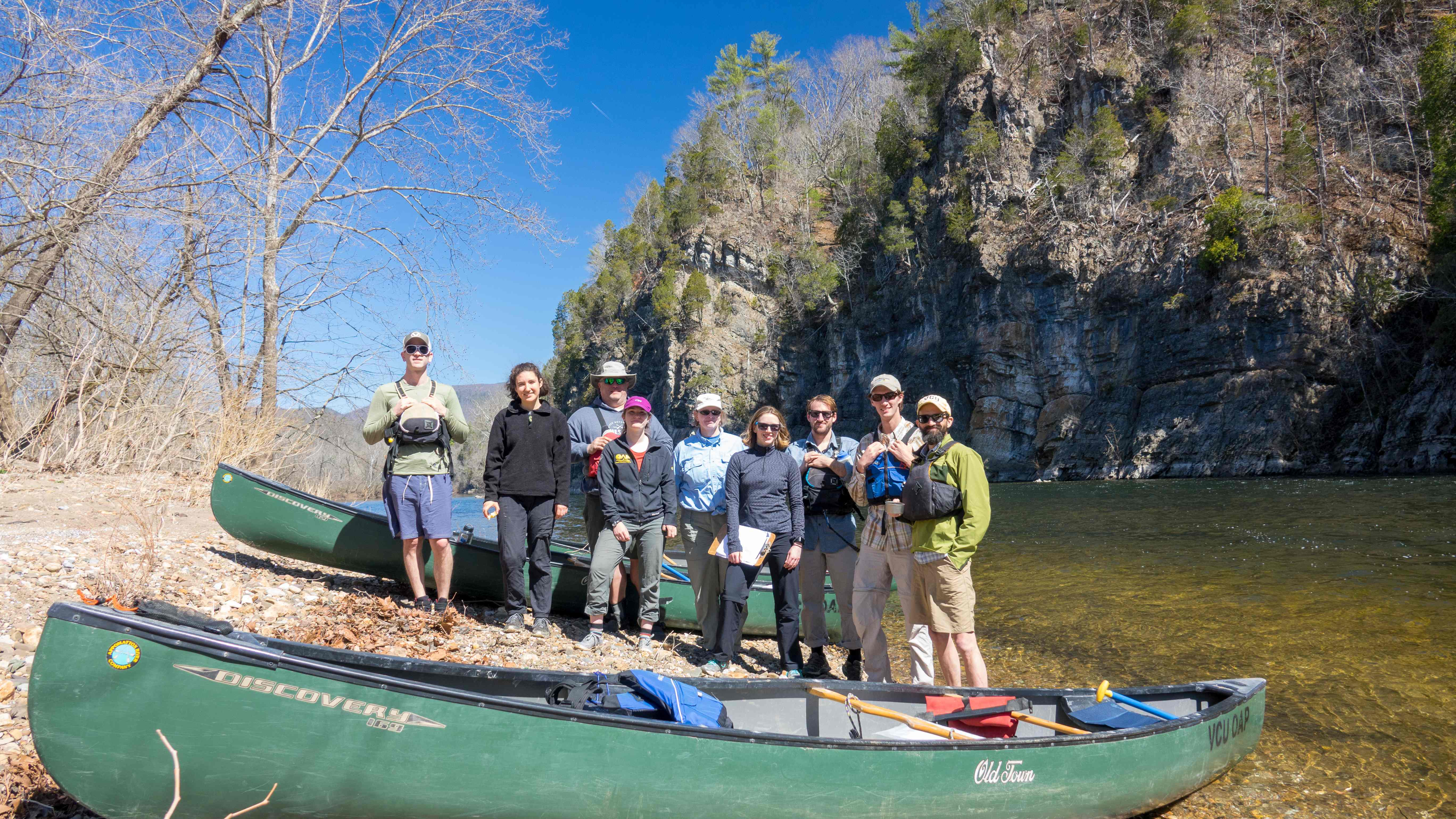 VCU students and instructors pose on the edge of a river for VCU River Studies Leadership Certificate program